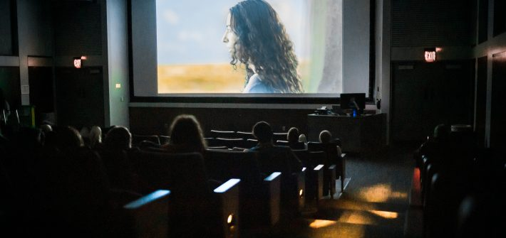 woman on a movie screen in front of audience