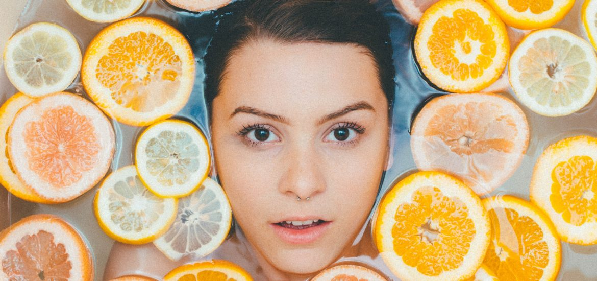 Woman in bathtub surrounded by sliced oranges