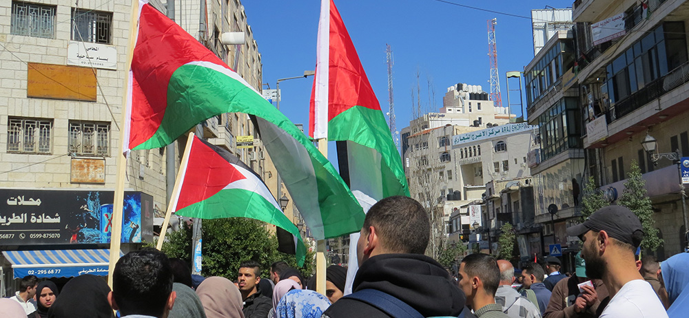 Palestinians raise their nation's flag during a protest in Ramallah, Palestine.