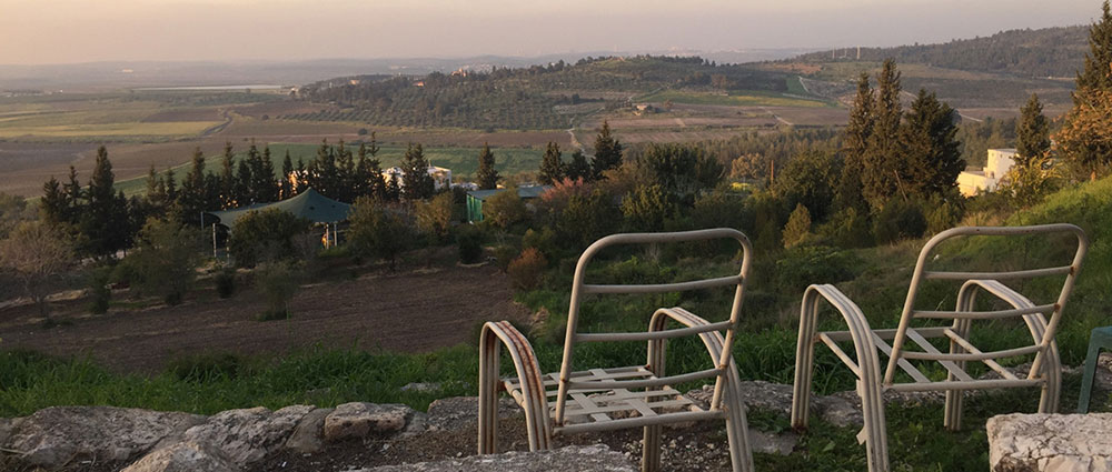Two empty chairs look over the Israeli landscape
