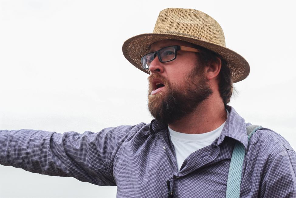 Adam Waddell, a tour guide from Kibbutz Ashdot Ya'akov, points to the Jordan River.