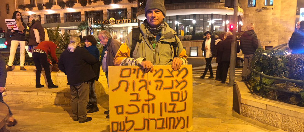 "A man stands in a square at night holding a sign with Hebrew writing that translates to ""Growing leadership with a wise heart which is connected to the people"""