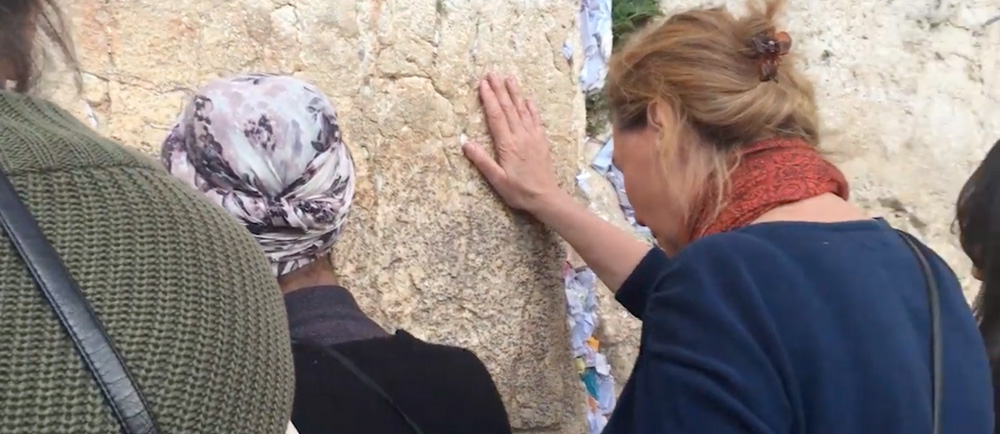 A woman stands at a wall, praying.