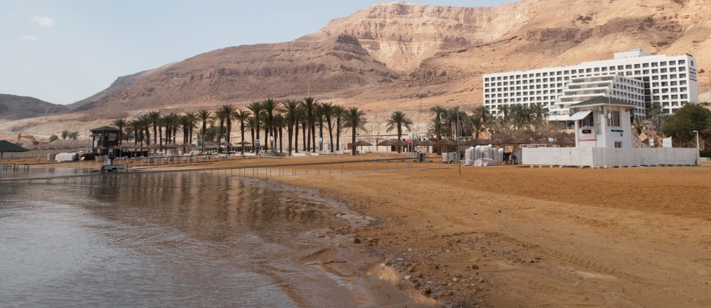 Image of a muddy beach next to a hotel resort.