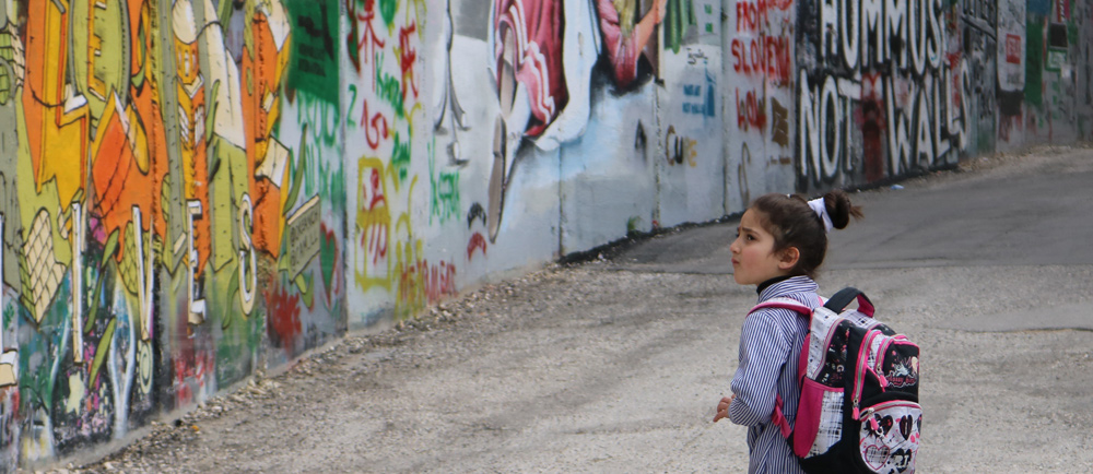 A young Palestinian girl looks up at the wall dividing the West Bank from Jerusalem.
